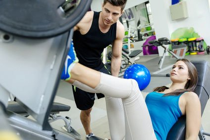 personal trainer assists woman on fitness equipment