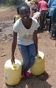 Young Kenyan girl carrying water jugs