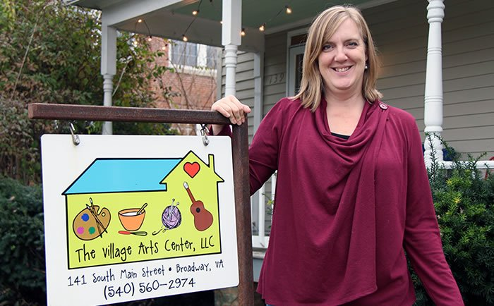 Dawn Murray with The Village Arts Center, LLC sign